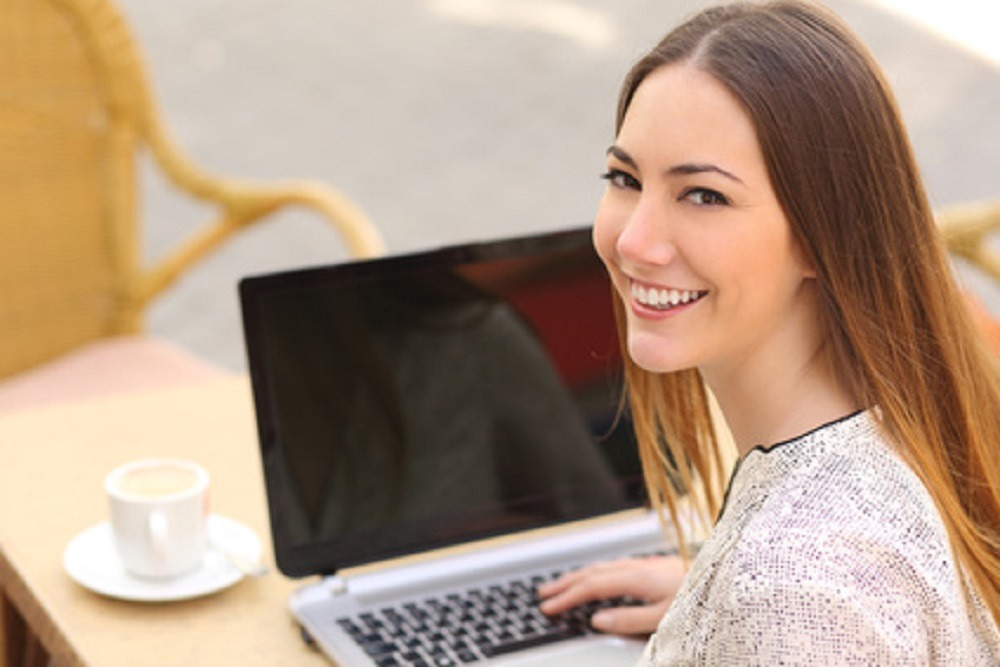 Happy woman using a laptop in a restaurant and looking at camera